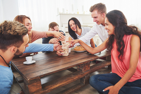 Top view creative photo of friends sitting at wooden table. Friends having fun while playing board game Stock Photo