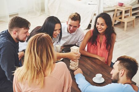 Group of creative friends sitting at wooden table. People having fun while playing board game