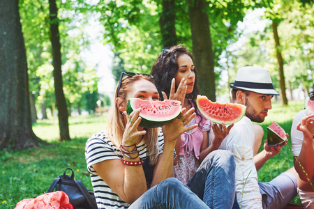 Group of friends having pic-nic in a park on a sunny day - People hanging out, having fun while grilling and relaxing