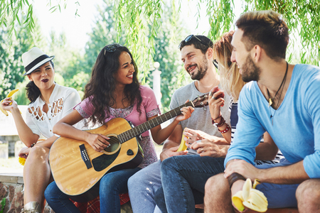 Group of happy friends with guitar. While one of them is playing guitar and others are giving him a round of applause