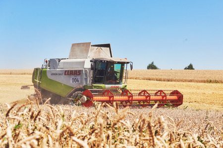 TERNOPIL - JULY 20: A modern combine harvester working a wheat field on July 20, 2017, in Ternopil.