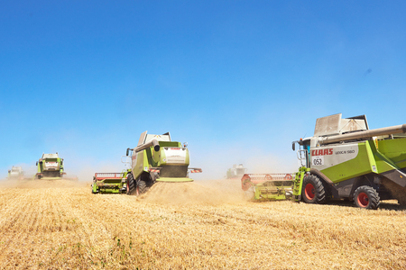 TERNOPIL - 20 luglio: alcuni combina un'andana nel mezzo di un campo di grano durante la vendemmia, il 20 luglio 2017, a Ternopil. Archivio Fotografico - 86464739