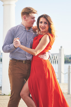 Happy beautiful woman in red dress and young man dance of on summer with lake in the background. Color contrast red and white 版權商用圖片