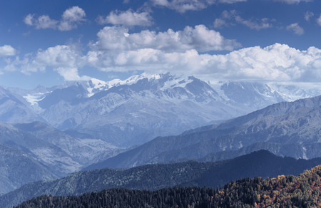 Fantastic snow-capped mountains in the beautiful cumulus clouds. Main Caucasian Ridge. Type Mount Ushba Meyer, Georgia Stock Photo