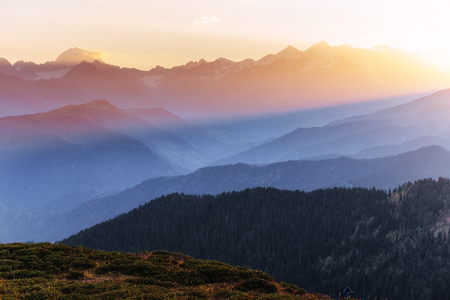 Sunset over snow-capped mountain peaks. The view from the mountains to Mount Ushba Mheyer, Georgia. Europe