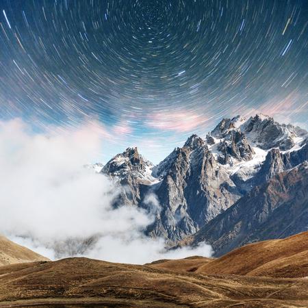 Fantastic starry sky. Snow-capped peaks. Main Caucasian Ridge. Mountain View from Mount Ushba Meyer, Georgia. Europe