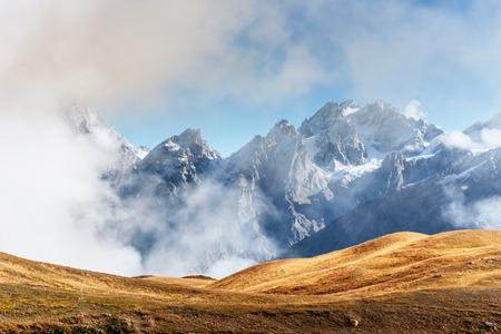 Autumn landscape and snow mountains in beautiful cumulus clouds. Main Caucasian Ridge. Type Mount Ushba Mheyer, Georgia Stock Photo