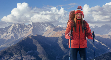 A woman with a backpack rest on top of the mountain and enjoy the views of the valley Stock Photo