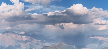 Fantastic snow-capped mountains in the beautiful cumulus clouds. Main Caucasian Ridge.