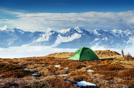Tent against the backdrop of snow-capped mountain peaks. The view from the mountains to Mount Ushba Mheyer, Georgia. Europe Stock Photo
