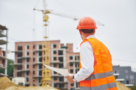 architectuur en huisvernieuwingsconcept - mens in helm en handschoenen met blauwdruk in fabriek