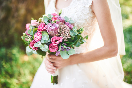 bride in a white dress holding a bouquet of purple flowers and greenery on the background of green grass Stock Photo