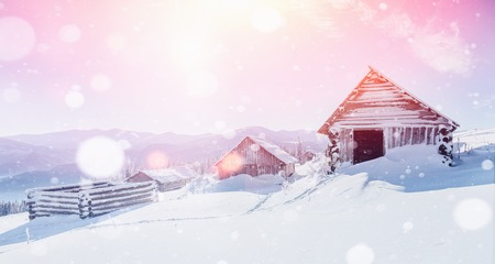 Hut in the mountains in winter, background with some soft highlights and snow flakes. Carpathians, Ukraine, Europe Reklamní fotografie - 91275896