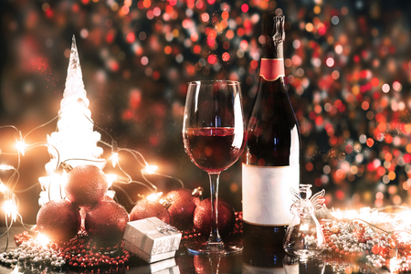 Christmas and New Year. Festive decorations, bottle of red wine and glass on the dark background. Happy New Year and Christmas. Bokeh light soft effect.