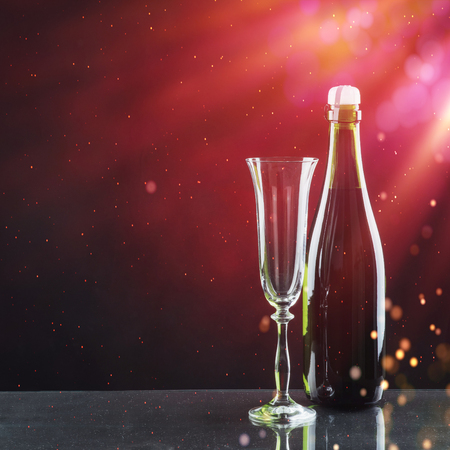 Glass and bottle of champagne on a dark background.
