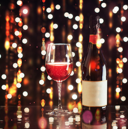 Red wine glass with bottle on background lights. Happy new year.