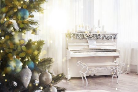 New Year decoration. Christmas tree near white piano at the window background. Bokeh light soft effect. Stock Photo