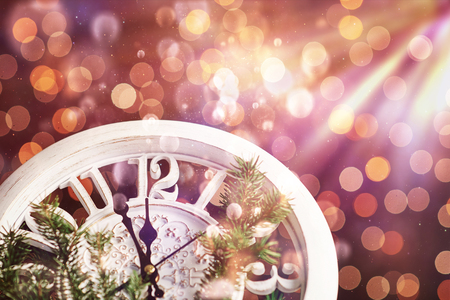 Happy New Year at midnight 2018, Old wooden clock with holiday lights and fir branches. Bokeh light soft effect.