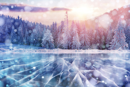 Blue ice and cracks on the surface of the ice. Frozen lake in winter mountains. It is snowing. The hills of pines. Winter. Carpathian Ukraine Europe.