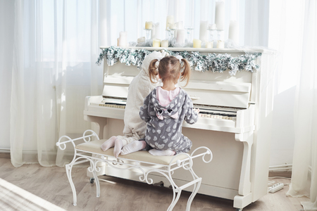 Two happy little girls in pajamas play the piano on Christmas day. Stock Photo