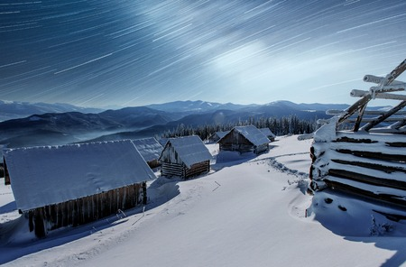 Night with stars. Christmas landscape. Wooden house in the mountain village. Night landscape in winter.