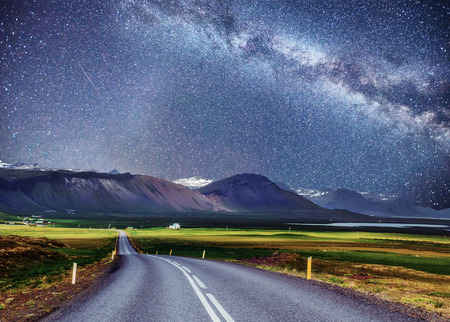 Starry Sky over the mountains. The asphalt road with white markings. Beautiful summer landscape. Soft filtering effect. Iceland. Stock Photo