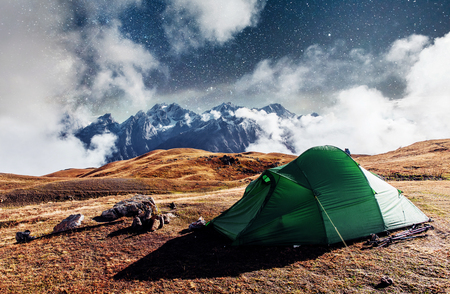 Fantastic starry sky. Tent against the backdrop of snow-capped mountain peaks. The view from the mountains to Mount Ushba Mheyer, Georgia. Europe. Stock Photo