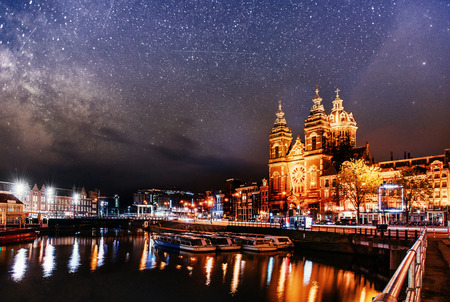 Beautiful night in Amsterdam. Night illumination of buildings and boats near the water in the canal.