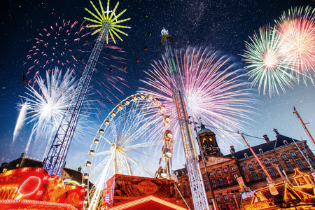 amusement park at the center of Amsterdam at night. Beautiful starry sky, majestic fireworks on the nightlife.