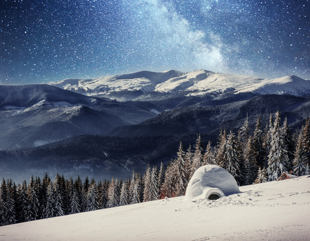 Yurt in the snow in the winter forest. Starry sky over the mountain peaks.