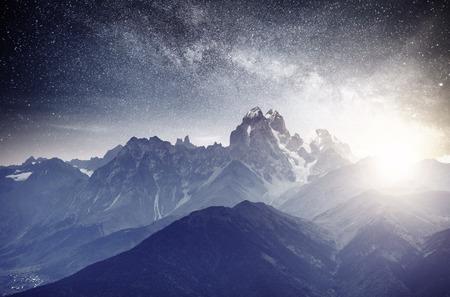 Fantastic starry sky. Autumn landscape and snow-capped peaks. Main Caucasian Ridge. Mountain View from Mount Ushba Meyer, Georgia. Europe. Stock Photo