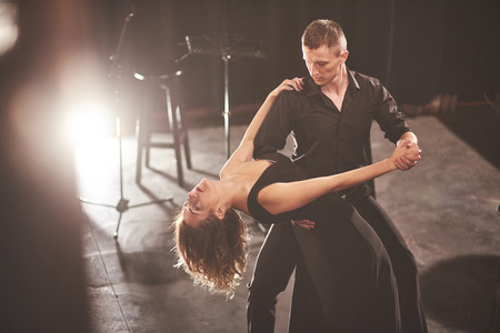 Skillful dancers performing in the dark room under the light. art concept of first love, passion, elegance. Valentines Day.
