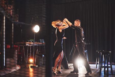 Hábiles bailarines actuando en la habitación oscura bajo la luz. concepto de arte de primer amor, pasión, elegancia. Día de San Valentín.