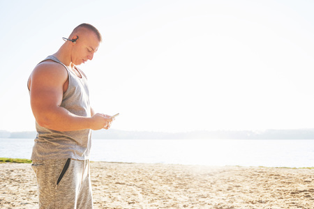 A athletic man looking at the seaside on the wild sand beach. Masculine and sporty male with naked torso is doing evening training at the sea cost. Summer work-out training outdoors. 스톡 콘텐츠 - 100245534