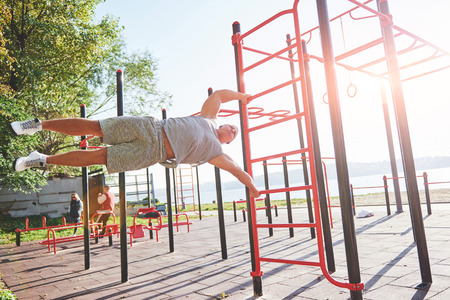 Muscular man with beautiful torso exercising on horizontal bars on a blurred park background. Young man doing pull-ups outdoors. Stock Photo