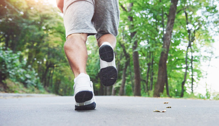 Outdoor cross-country running in concept for exercising, fitness and healthy lifestyle. Close up of feet of young runner man running along road in the park. Stock Photo