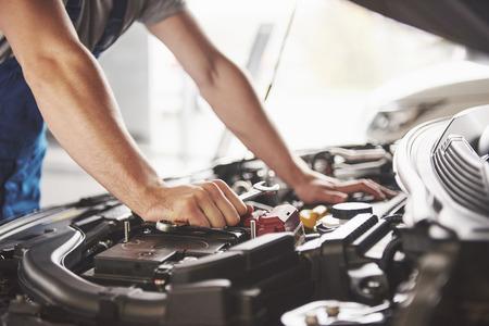Meccanico auto che lavora in garage. Servizio di riparazione.