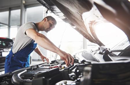 Immagine che mostra il lavoratore di servizio di auto muscolare che ripara il veicolo.