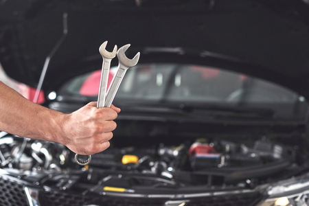 Mechanic holding pair of wrenches at the repair garage.