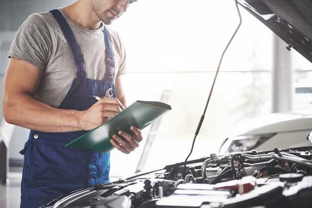 Portret mechanika przy pracy w swoim garażu - koncepcja serwisu, naprawy, konserwacji i ludzi. Zdjęcie Seryjne