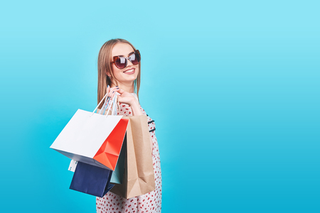 Portrait of young happy smiling woman with shopping bags on the Blue Background.
