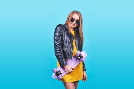 Attractive tanned girl with smile in face wears black leather jacket posing with pleasure. Indoor photo of lovely woman in sunglasses standing with skateboard on blue background.