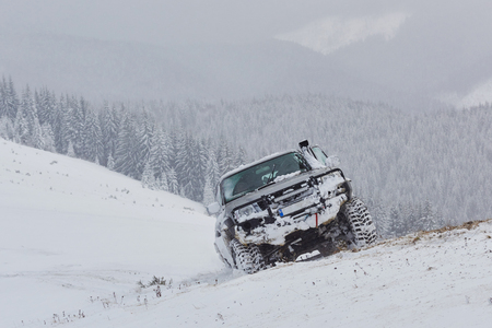 SUV rides on a winter mountians driving risk of snow and ice, drifting.