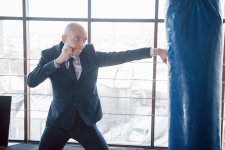 An angry bald businessman beats a boxing pear in the gym. concept of anger management.
