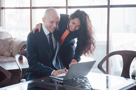 We already have great results. Young beautiful woman pointing at laptop with smile and discussing something with her coworker while standing at office. Stock Photo