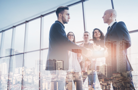 Two confident business man shaking hands during a meeting in the office, success, dealing, greeting and partner concept. Double exposition, panorama of modern city.