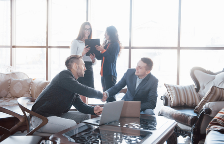 Welcome on board. Two handsome men shaking hands with smile at office with their coworkers. Young team of coworkers making great business discussion in modern coworking office. Teamwork people concept.