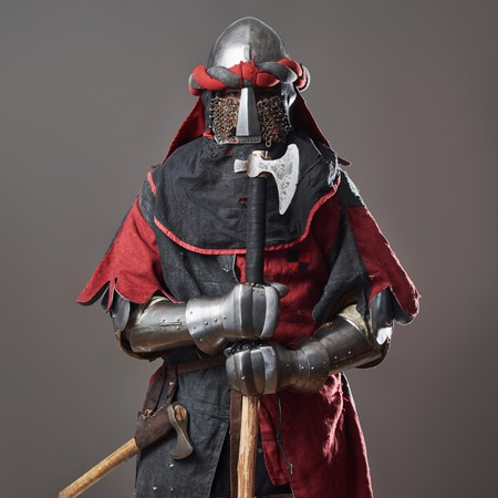Medieval knight on grey background. Portrait of brutal dirty face warrior with chain mail armour red and black clothes and battle axe. Stock Photo
