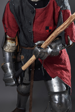 Medieval knight on grey background. Portrait of brutal dirty face warrior with chain mail armour red and black clothes and battle axe. Stockfoto - 101403675