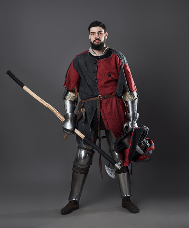 Medieval knight on grey background. Portrait of brutal dirty face warrior with chain mail armour red and black clothes and battle axe. Stockfoto - 101403687